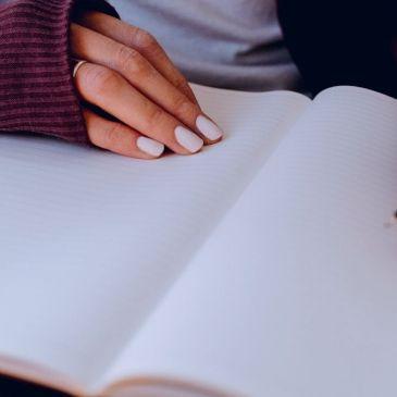 Writer holding a pen over a notebook